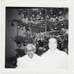 Elderly housekeeper sits beside a Christmas tree