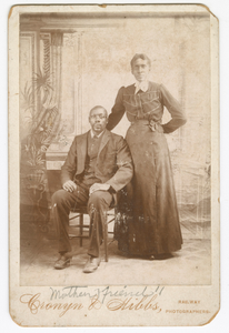 Photograph of a man sitting down with a woman standing next to him