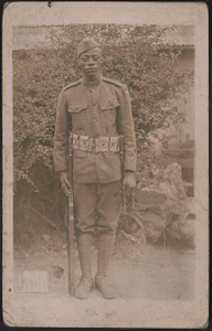 [Unidentified African American soldier in uniform and overseas cap with rifle and knife hanging from cartridge belt]
