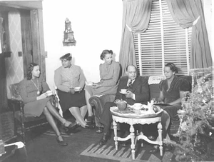 Man and women seated in living room drinking coffee.