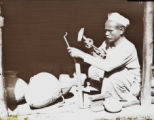 Craftsman making vessels, India, ca. 1930