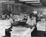 [African American female workers at the Bureau of Engraving and Printing, with stacks of currency : paper photoprint]