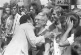 "Andrew Young leaning toward an elderly woman while shaking hands with another person in a crowd in downtown Atlanta, Georgia, during the Democratic National Committee's regional conference, ""Victory '68."""