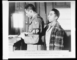 Cpl. Andrew Johnson is shown fingerprinting one of the civilian workers at the Tuskegee Army Flying School