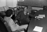 Mayor Richard Arrington talking with man in a conference room on the day of his inauguration as the first African American mayor of Birmingham, Alabama.