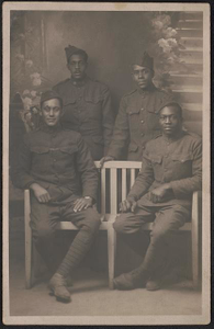 [Four unidentified African American soldiers in uniforms and overseas caps in front of painted backdrop]
